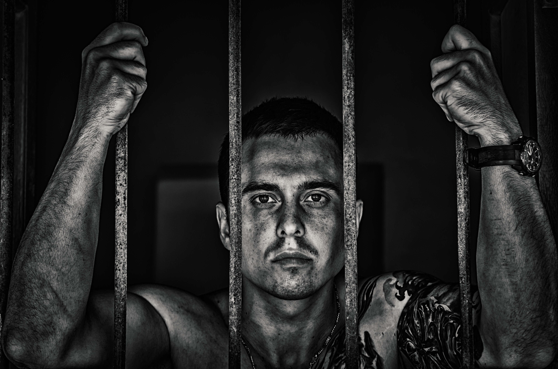 Du darfst dich beruflich neu erfinden! Zu sehen ist ein Mann hinter Gittern als Sinnbild für die lebenslange Gefangenschaft im gleichen Beruf.